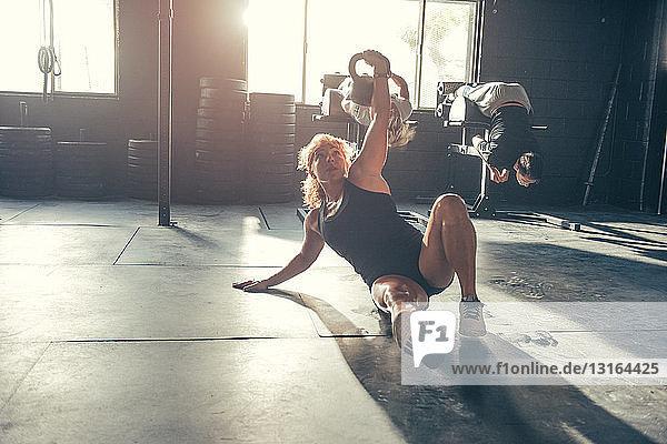 Frau trainiert mit Kettlebell im Fitnessstudio