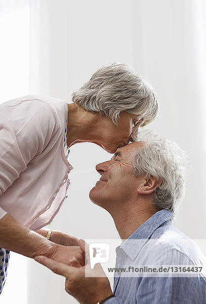 Ältere Frau beugt sich  um den Mann zu küssen
