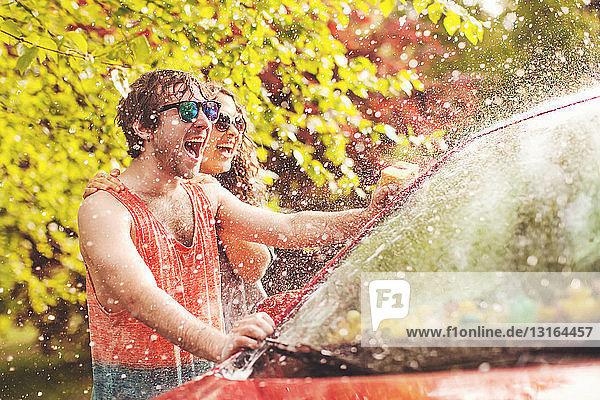 Junges Paar beim Autowaschen