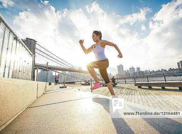 Läuferin läuft am Flussufer eine Treppe hinauf  New York  USA