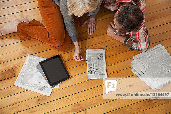 Paar macht Kreuzworträtsel auf Holzboden