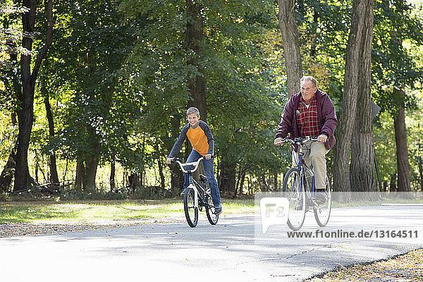 Älterer Mann und Enkel radeln durch Wälder