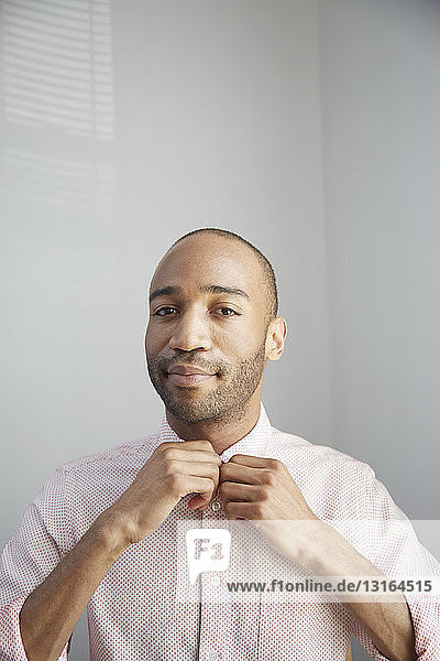 Portrait of man buttoning up shirt looking at camera smiling