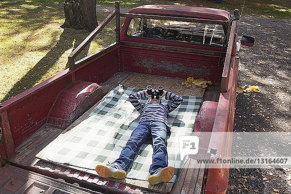 Junge  der durch ein Fernglas schaut  während er auf dem Rücksitz eines Pick-ups im Wald liegt