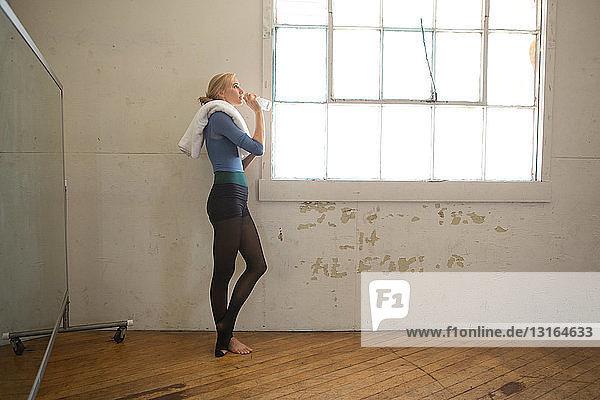 Portrait of female dancer drinking water