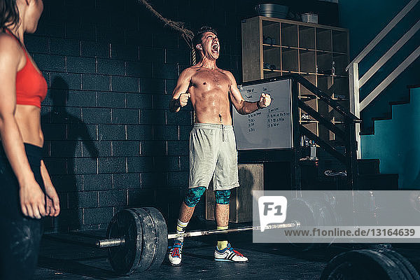 Mann ballt die Fäuste beim Langhanteltraining im Fitnessstudio