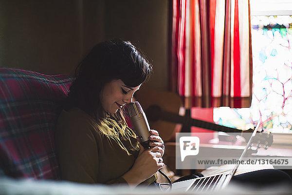 Frau mit Mikrofon und Laptop