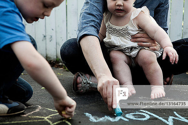 Mutter und zwei Kinder schreiben mit Kreide auf dem Boden