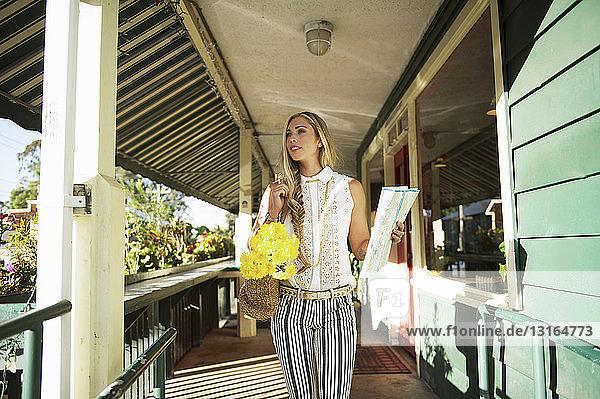 Junge Frau mit Karte in der Veranda