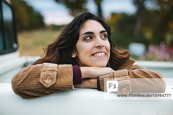 Young woman in back of truck  leaning on edge of truck  smiling  looking away