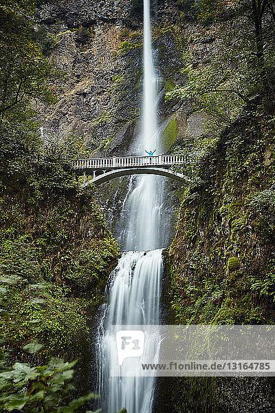 Male hiker crossing footbridge over Multnomah Falls  Oregon  USA