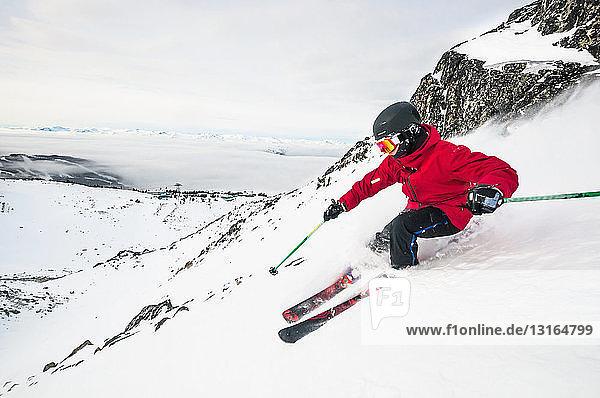 Seitenansicht eines jungen Mannes beim Skifahren auf einem verschneiten Berg  Whistler Blackcomb Skigebiet  Britisch-Kolumbien  Kanada