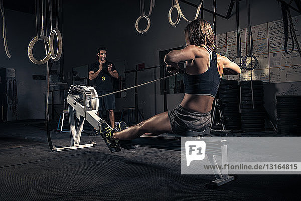 Frau benutzt Rudergerät im Fitnessstudio