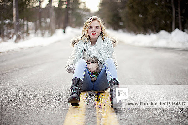 Young woman sitting on road through forest