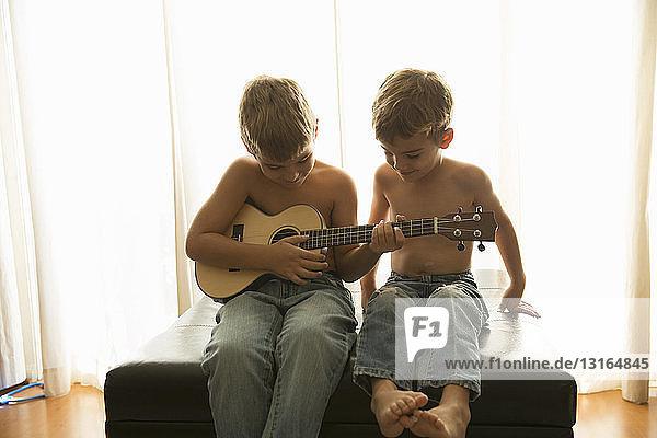 Brüder spielen zu Hause Gitarre