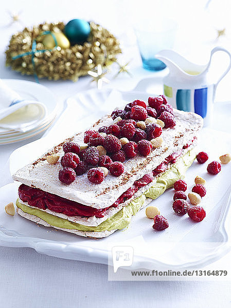 Tray of raspberry macadamia vacherin layer cake on decorated table