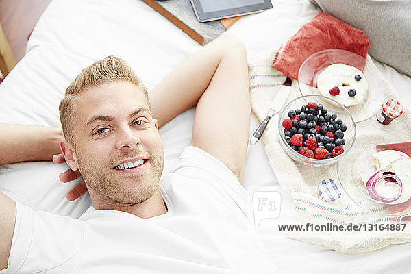 Man lying on bed  hands behind head looking at camera smiling