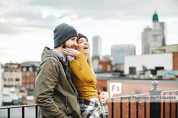 Young couple laughing on city rooftop terrace