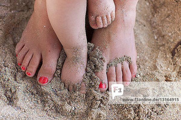 Mutter mit nackten Füßen ihrer Tochter im Sand Mutter mit nackten Füßen ihrer Tochter im Sand