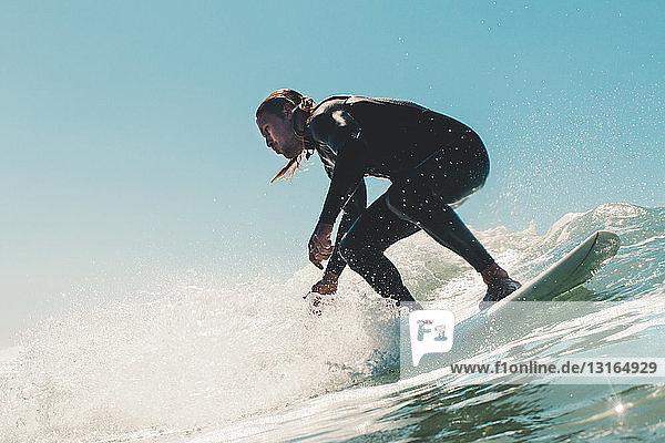 Junger Mann beim Surfen  niedriger Blickwinkel