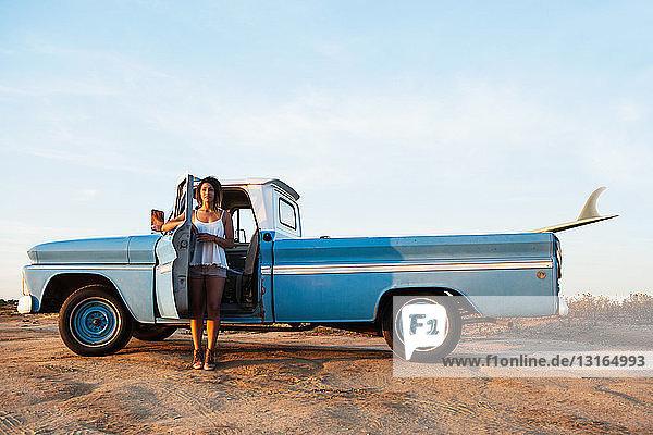 Porträt einer jungen Surferin  die sich an die Tür eines Pickup-Trucks lehnt  Leucadia  Kalifornien  USA