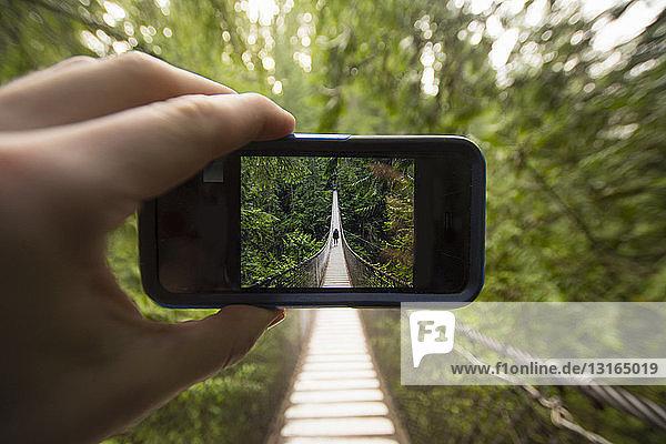 Smartphone in der Hand eines Mannes mit dem Bild einer Frau auf der Lynn-Canyon-Hängebrücke  North Vancouver  British Columbia  Kanada