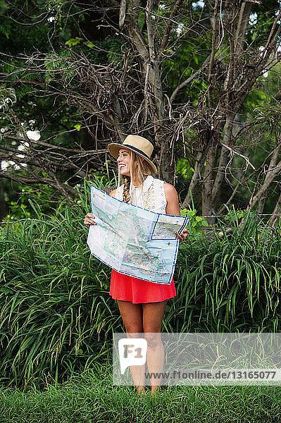Junge Frau mit Karte im Wald