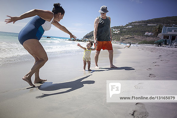 Kleinkind und Großeltern spielen am Strand