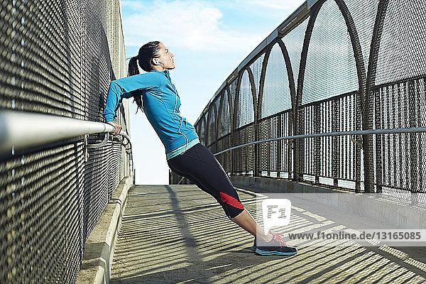 Mid adult woman stretching on bridge