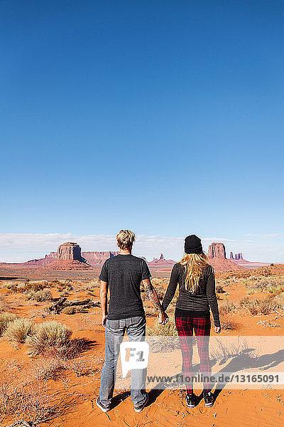 Rückansicht eines Touristenpaares  das sich an den Händen hält  Monument Valley  Utah  USA