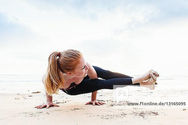 Mittlere erwachsene Frau in Yogastellung am Strand