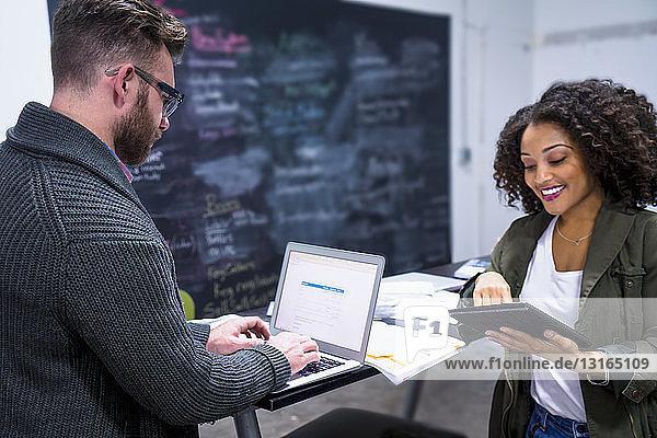 Kollegen am Arbeitsplatz mit digitalem Tablet und Laptop lächeln