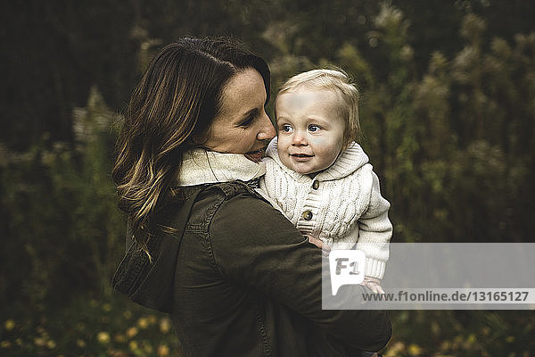 Waist up side view of mother holding baby boy in autumn