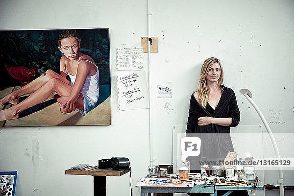 Mittlere erwachsene Frau im Atelier des Künstlers stehend  Porträt