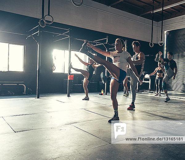 Männer und Frauen trainieren gemeinsam im Fitnessstudio