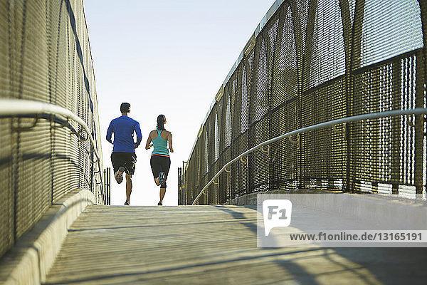 Mann und Frau laufen über die Brücke
