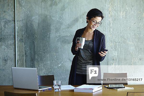Junge Geschäftsfrau betrachtet Smartphone im Büro