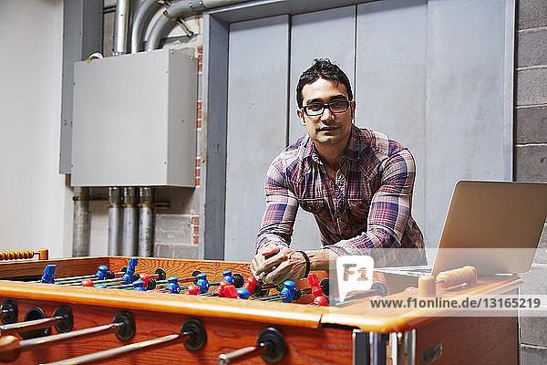 Porträt eines jungen Mannes  der sich an einen Tischfussball lehnt