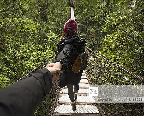Frau auf der Lynn-Canyon-Hängebrücke  die die Hand des Mannes hält  North Vancouver  British Columbia  Kanada
