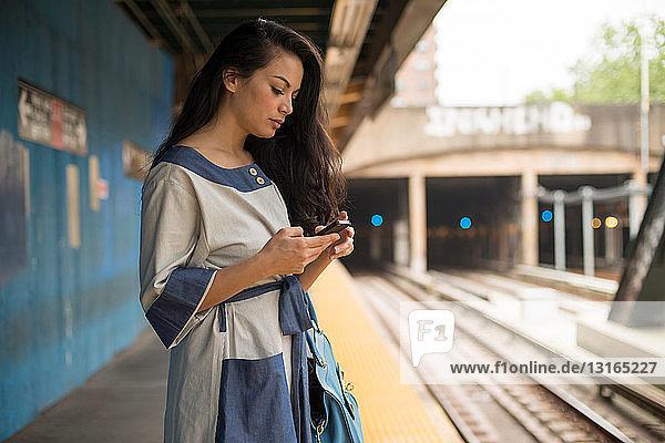 Mid adult women using mobile phone on subway platform  Brooklyn  New York
