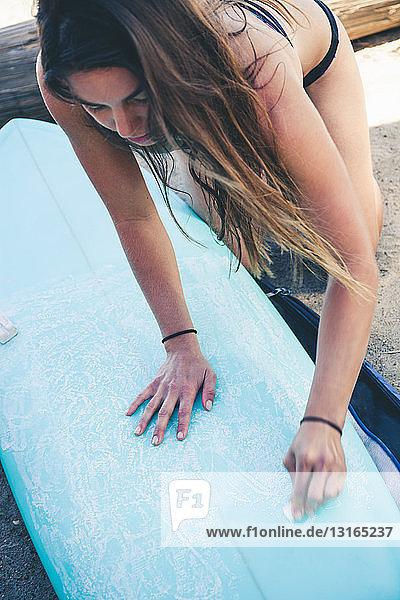 Frau wachst Surfbrett