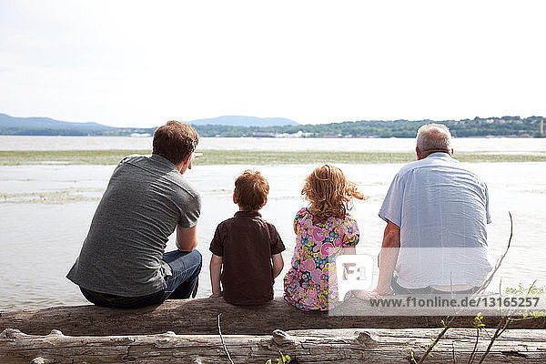 Kinder am Fluss mit Vater und Großvater