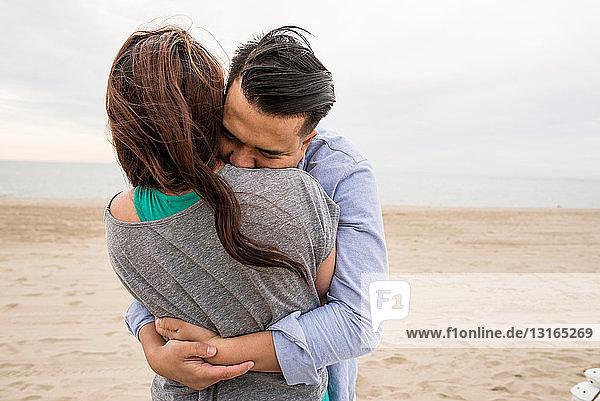 Junges Paar umarmt sich am Strand