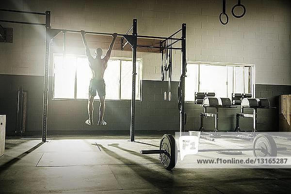 Junger Mann trainiert an der Übungsstange in der Turnhalle