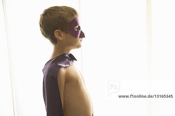 Junge mit Umhang und Maske zu Hause