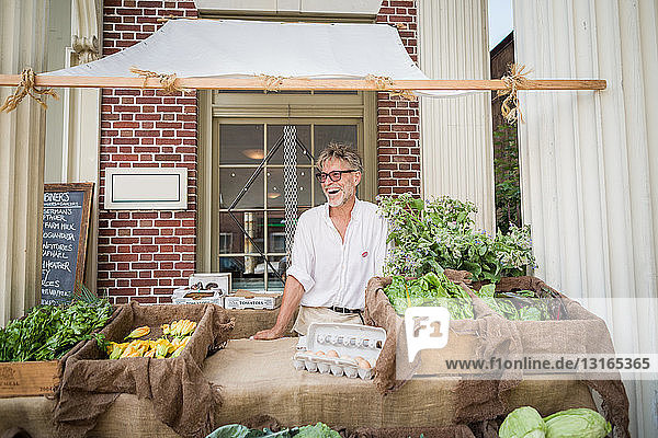 Farmer selling organic eggs and vegetables on stall outside store