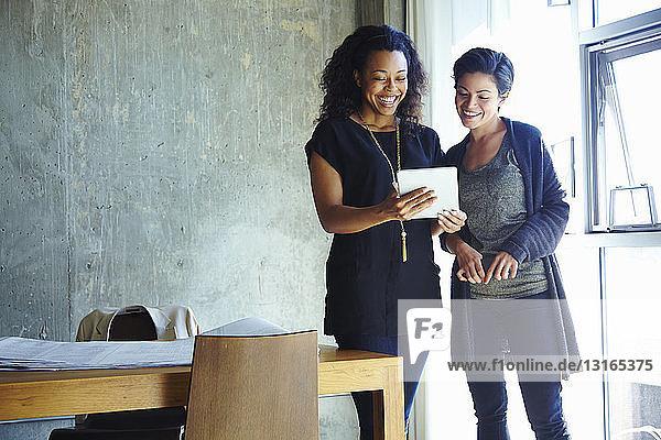 Zwei junge Geschäftsfrauen schauen sich digitales Tablet an
