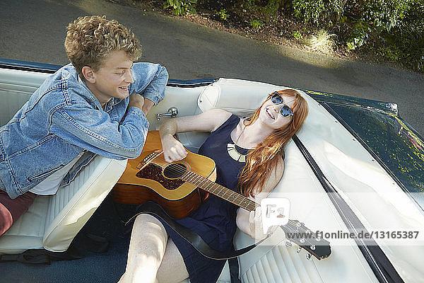 Junge Frau spielt Gitarre für ihren Freund auf dem Rücksitz eines Oldtimer-Cabrios