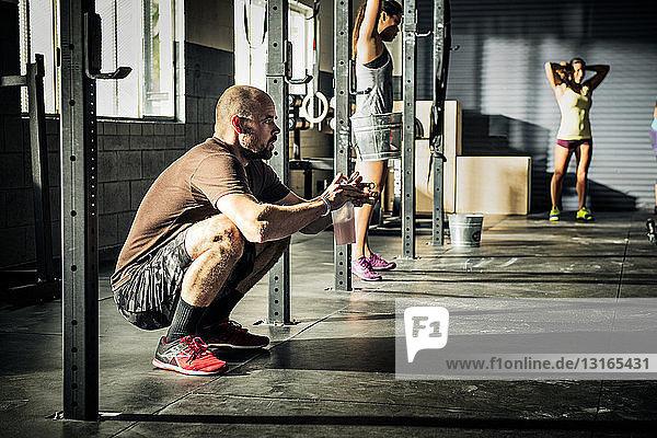 Männer und Frauen wärmen sich für das Training in der Turnhalle auf