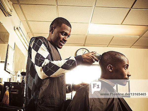 Barbier im traditionellen Friseurladen rasiert dem Mann den Kopf